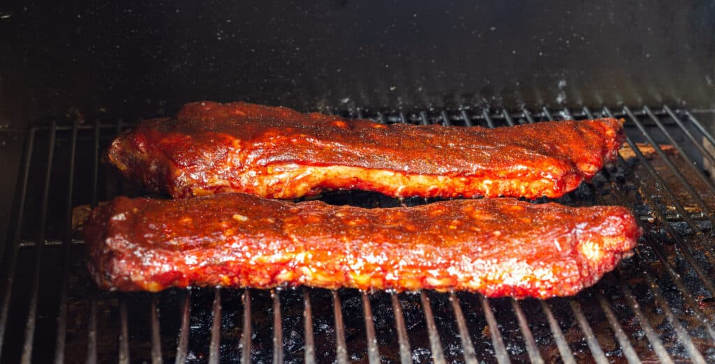 Spare ribs in a smoker with sauce