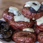 A pile of smoked juicy lucy hamburgers topped with provolone cheese and sitting next to some cooked mushrooms.