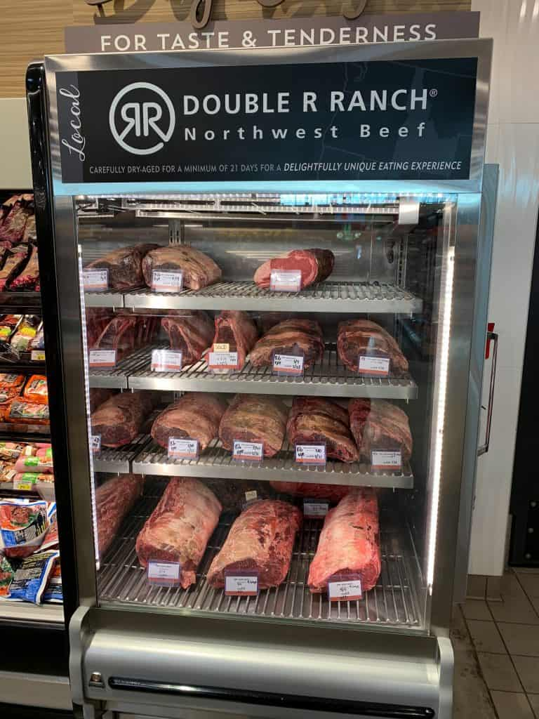 Dry aged beef cooler at Albertson's on Broadway, proudly displaying 13 different cuts of meat being dry aged.