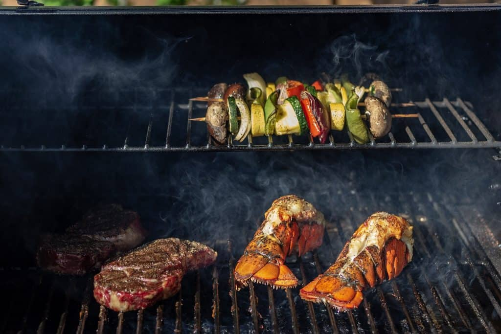 Dry aged ribeyes, vegetable kabobs, and lobster tails on a grill. Smoke can be seen lightly swirling around the food.