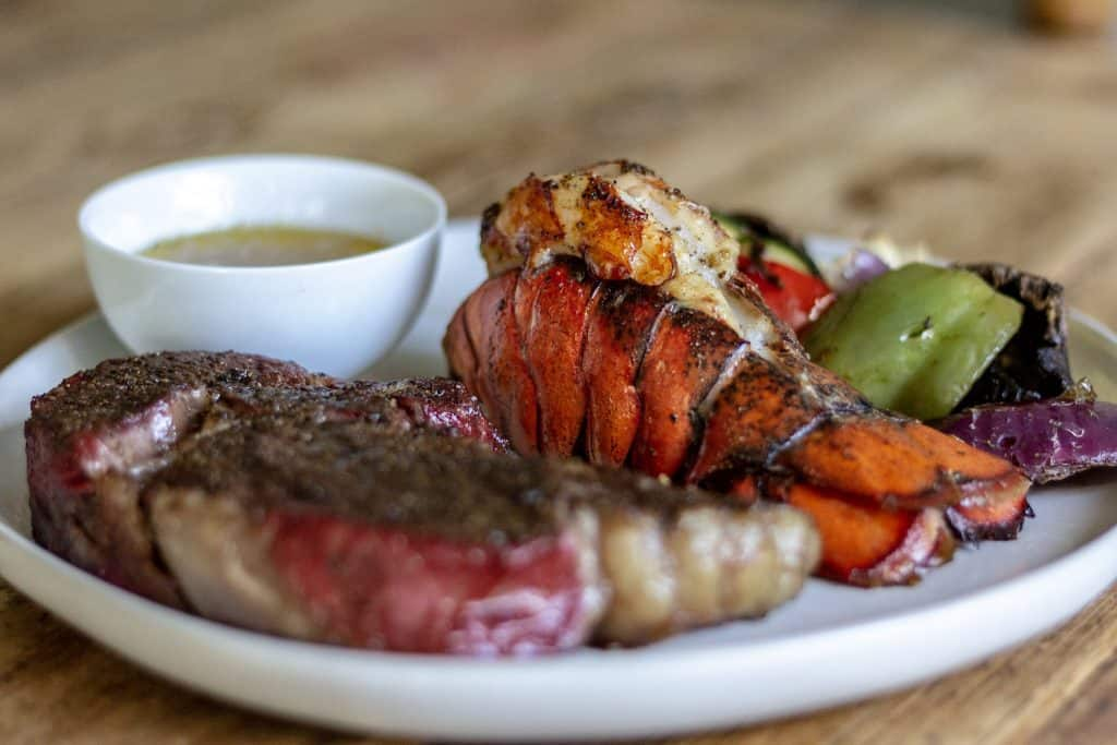 Smoked Lobster Tail highlighted next to a steak. This article talked about how to cook dry aged steak.