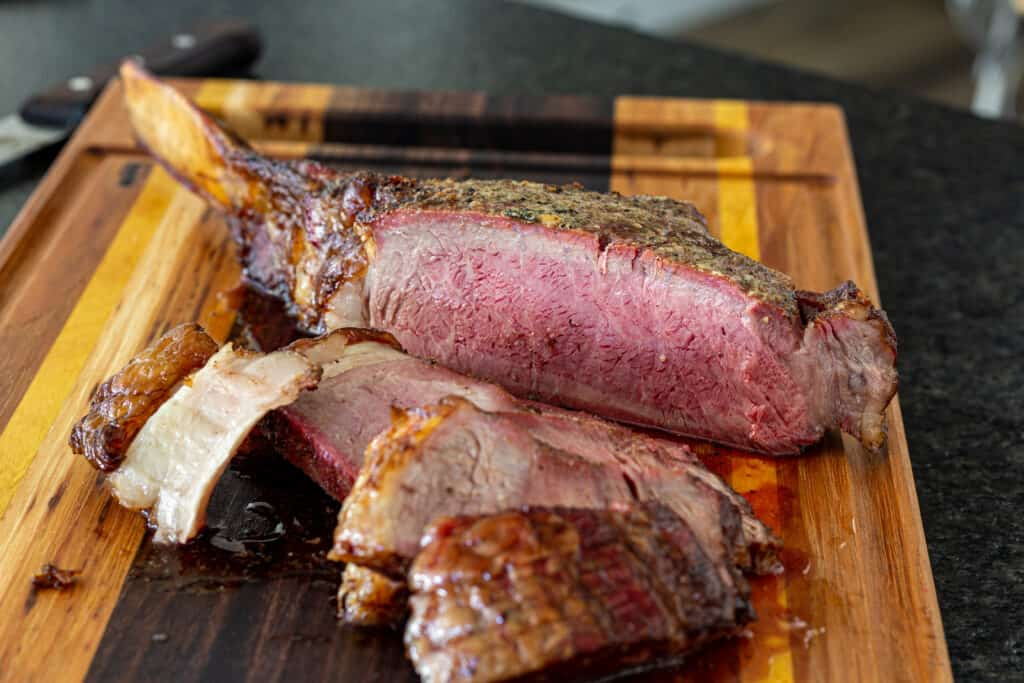 Sliced smoked tomahawk steak on a cutting board. The steak is medium rare and a smoke ring is present.