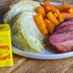 A Plate of Smoked Corned Beef Brisket, carrots, and cabbage with a container of Colman's Dry Mustard