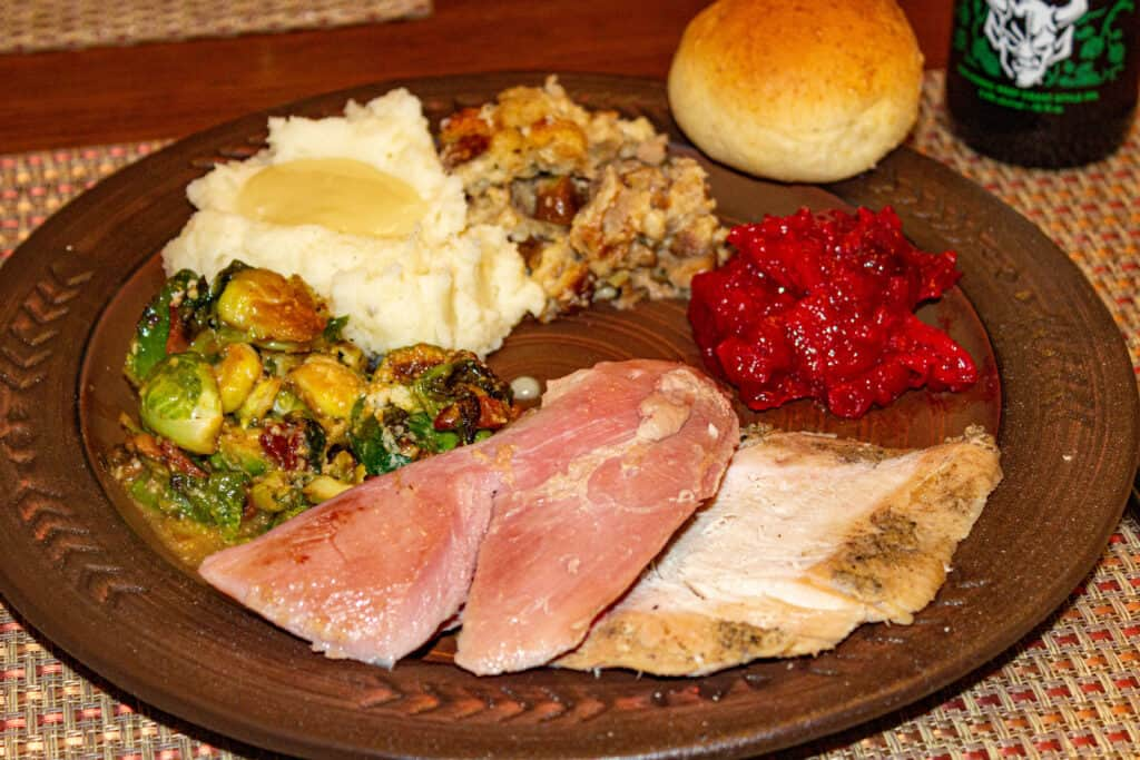 smoked turkey slices on a plate with traditional sides - how to smoke a turkey