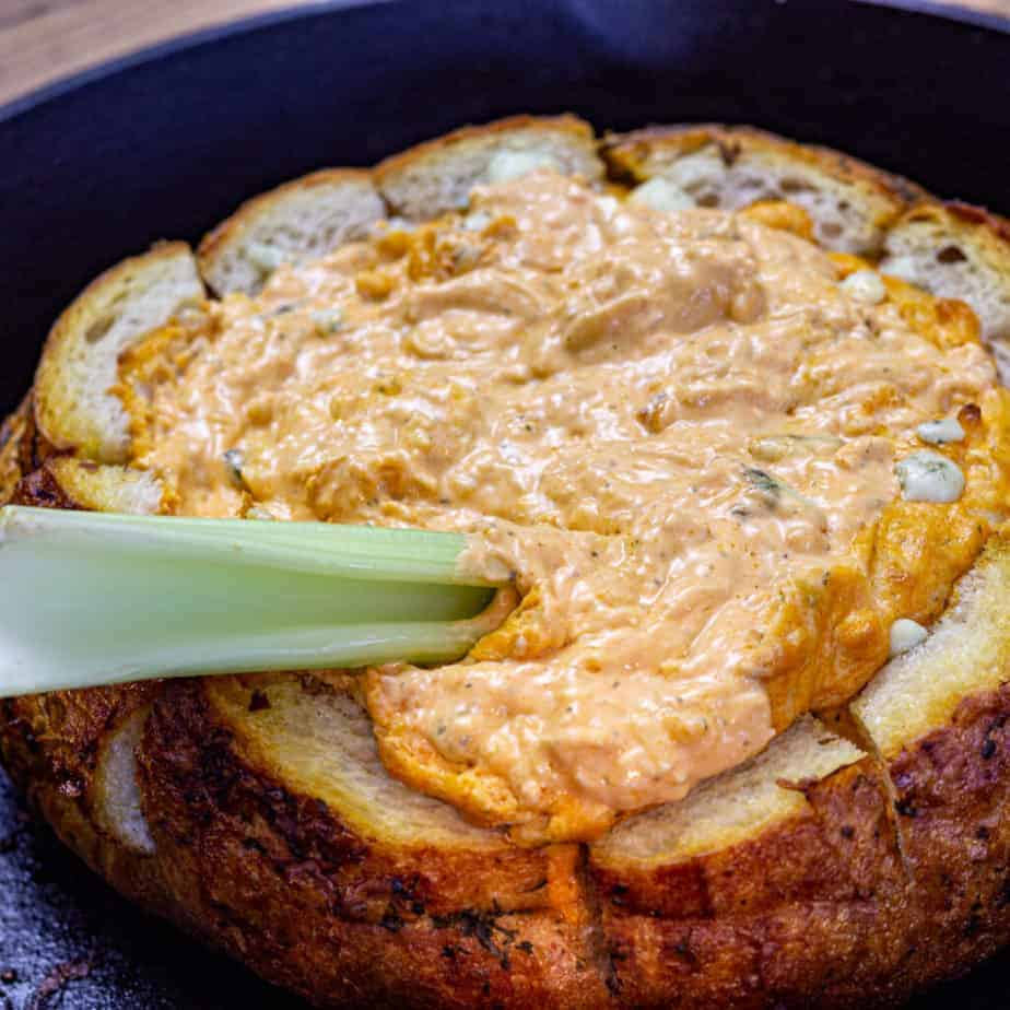 smoked buffalo chicken dip recipe in a bread bowl with celery
